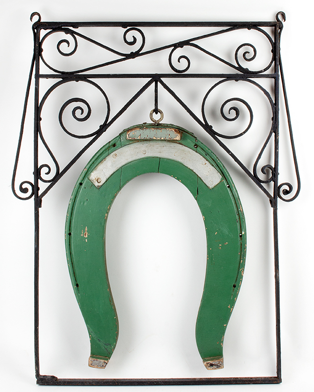 Trade Sign, Farrier, Horseshoe, Carved & Painted Shoe Unknown Maker, circa 1880-1900 Carved horseshow hangs within the scrolled wrought iron frame, entire view