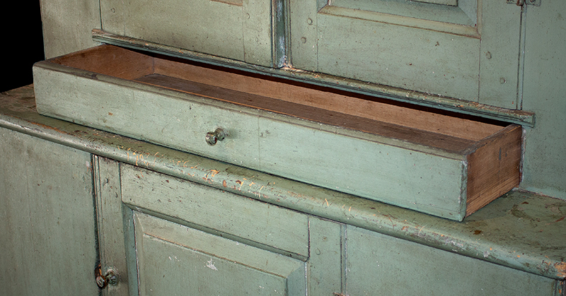 Antique Step-back Cupboard in Historic Surface, Raised Panel Doors, Small Size New England, Likely Maine or New Hampshire, circa 1780-1820 Basswood, very early sage green paint over gray over red, drawer detail